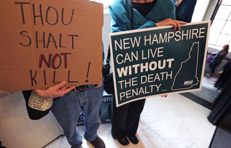 Demonstranten houden borden omhoog voor de stemming. 'New Hampshire kan leven zonder de doodstraf' staat er, net als 'je zal niet moorden', verwijzend naar de tien geboden.