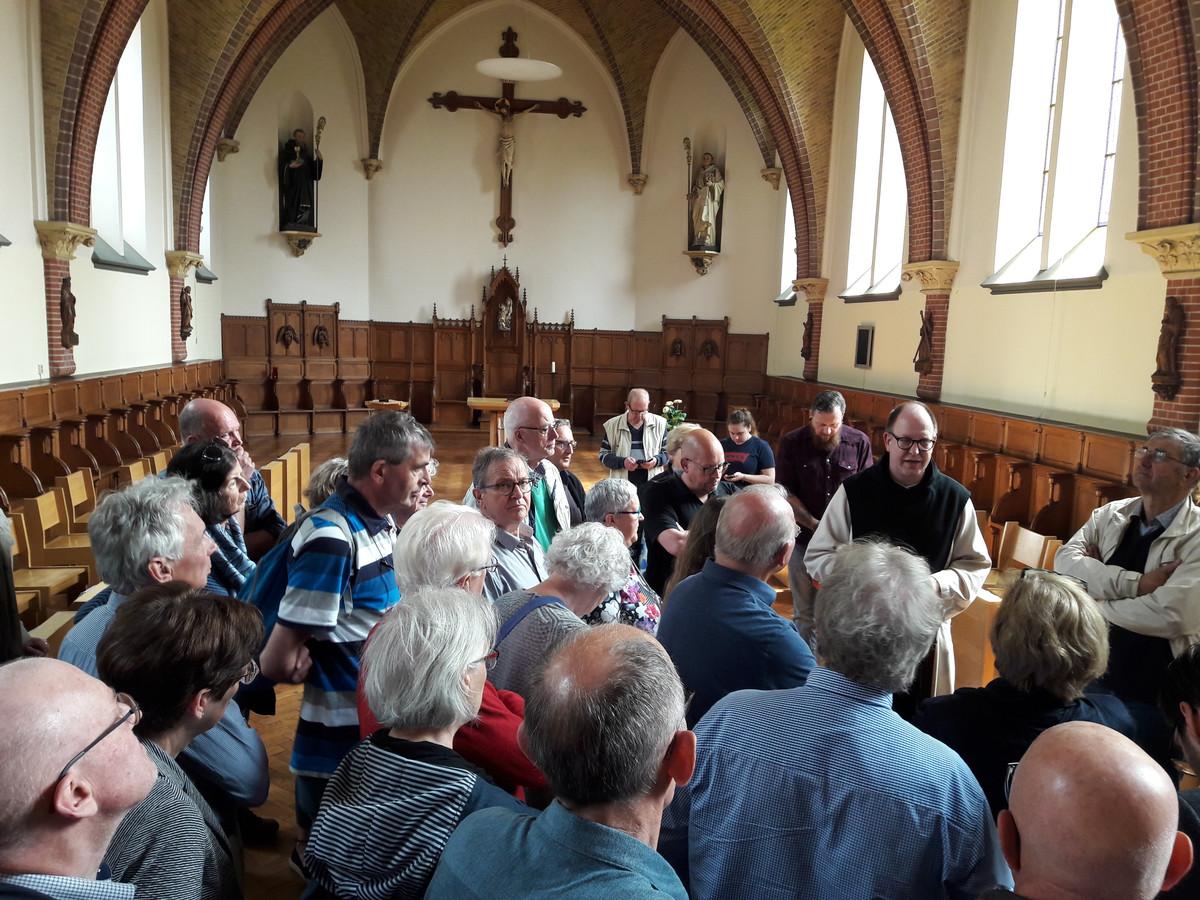 In het oratorium van de abdij van Koningshoeven volgen op Open Kloosterdag 2019 belangstellenden de uitleg van dom Bernardus, vader abt