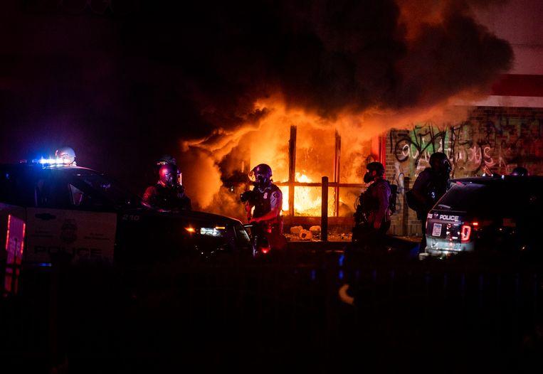 Bij protesten in Minneapolis op 27 mei zette de politie traangas en rubberen kogels in. Winkels werden geplunderd en in brand gestoken.  Beeld Getty Images