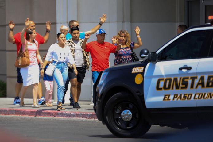 Met de handen in de lucht verlaten mensen die tijdens de schietpartij aanwezig waren het gebouw van de Walmart.