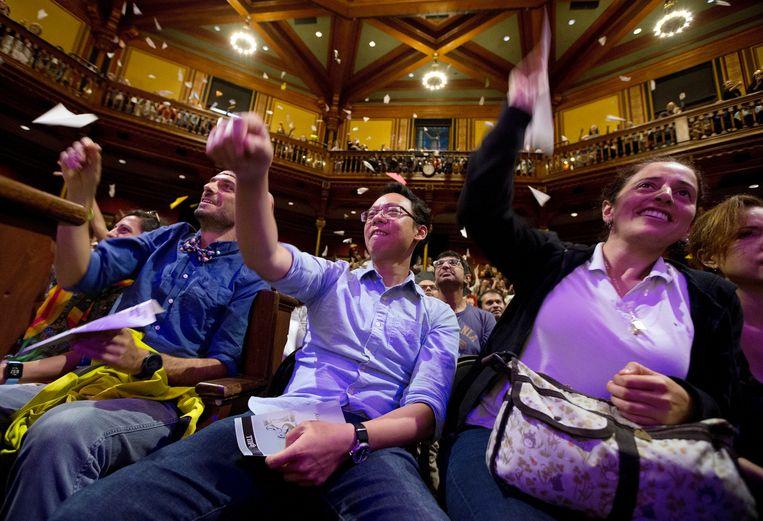 Toeschouwers vouwen papieren vliegtuigjes tijdens de uitreiking van de Ig Nobelprijzen van 2018 aan de Harvard-universiteit. Beeld AP