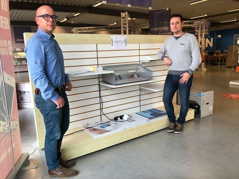 Zaakvoerder Jurgen Sas en shop manager Gert Sleeuwagen bij de leeggeroofde rekken.