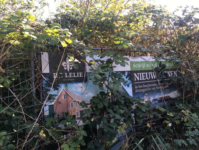 Het promotiebord van De Lelie tegen het hek waarmee het terrein, waar ooit schuren stonden, is afgesloten.