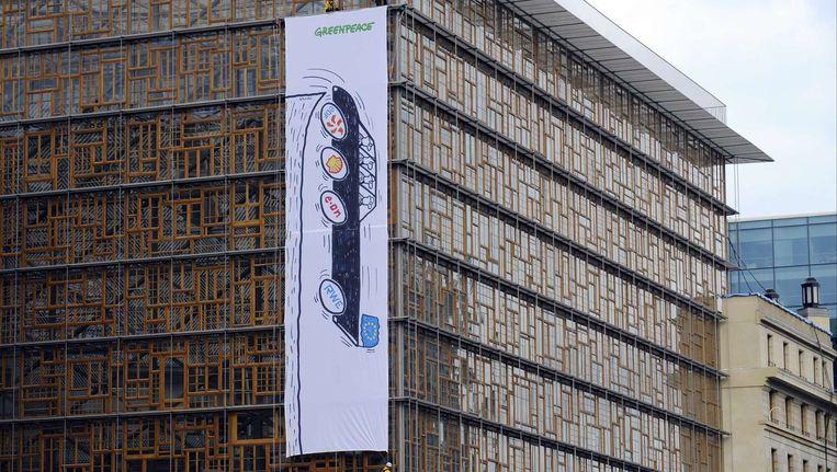 Spandoek van Greenpeace met daarop een zwarte dienstauto van de Europese Unie die een afgrond inrijdt. Beeld afp