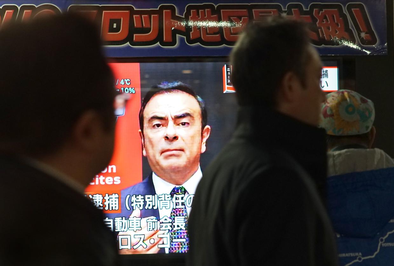 Voorbijgangers kijken in Tokio naar het nieuws over Nissan-Renault-topman Carlos Ghosn.  Beeld null