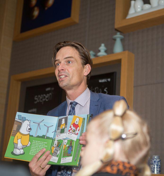 Wethouder Alwin te Rietstap leest voor uit het boek met  de besparingstips van beer Tad.