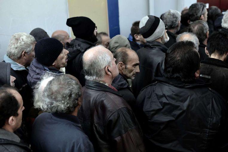 Armen en daklozen in de rij voor een gratis kerstdiner, aangeboden door de stad Athene. Beeld reuters