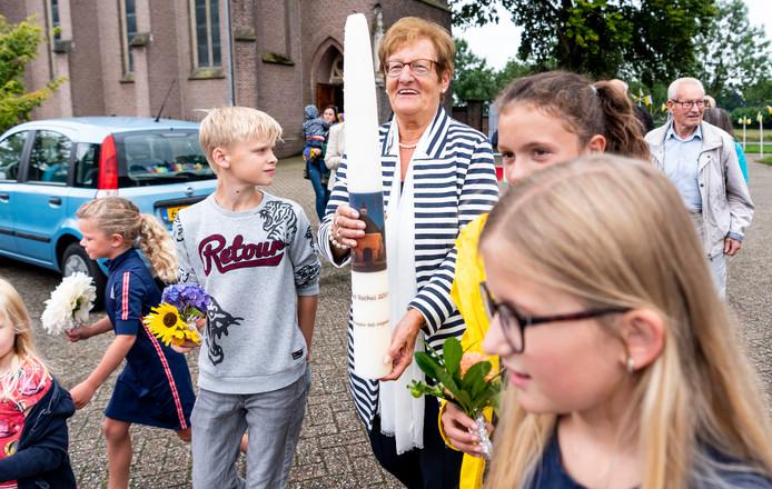 Bets Wiegmans-Strik draagt de Sint Rochuskaars samen met kinderen met bloemen.