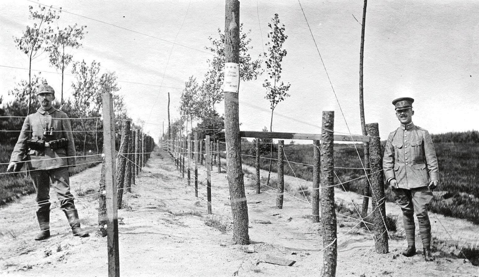Duitse en Nederlandse grenswacht bij de dodendraad.