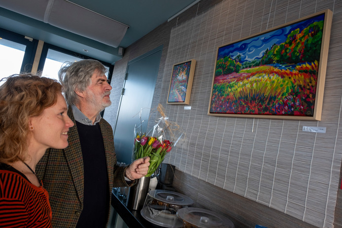 Wim Hofman kijkt met maakster Wieteke Hendrikx naar een net door hem onthuld 'kleurig, optimistisch' schilderij van het Nollebos.