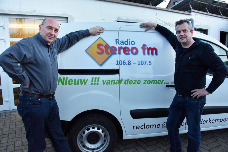 Stefan De Wilde en Marc Jansens bij het logo van hun nieuwe zender.