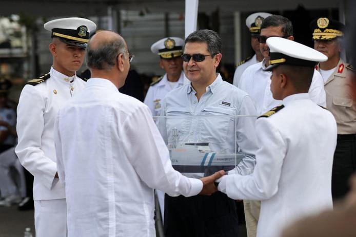 De Hondurese president Juan Orlando Hernández (midden) vrijdag tijdens de overdracht van een militaire patrouilleboot die het land van Israël heeft gekocht.