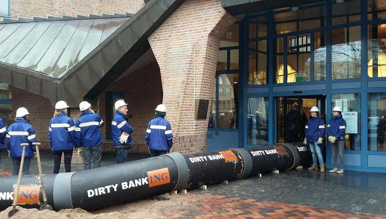 Actievoerders van Greenpeace voor het ING hoofdkantoor in Zuidoost. Beeld Bart van Zoelen