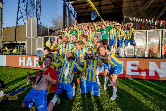 De spelers van RKC, met Hans Mulder rechtsonder, vieren het feest met hun fans in het uitvak.
