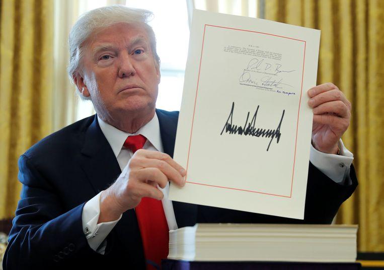 President Trump toont zijn omstreden belastingplan na ondertekening in het Witte Huis. Beeld REUTERS