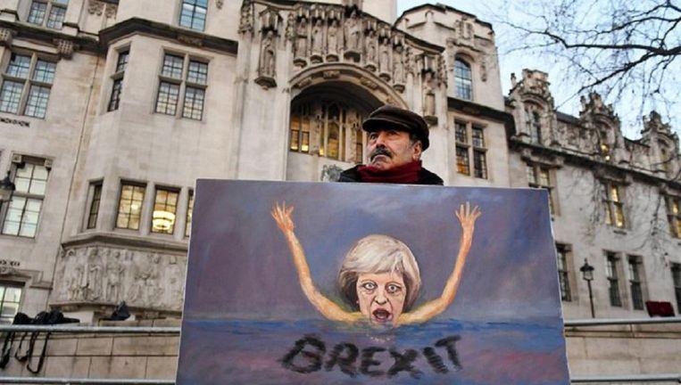 Politiek kunstenaar Kaya Mar staat met een schilderij van Theresa May voor het Britse Hooggerechtshof Beeld epa