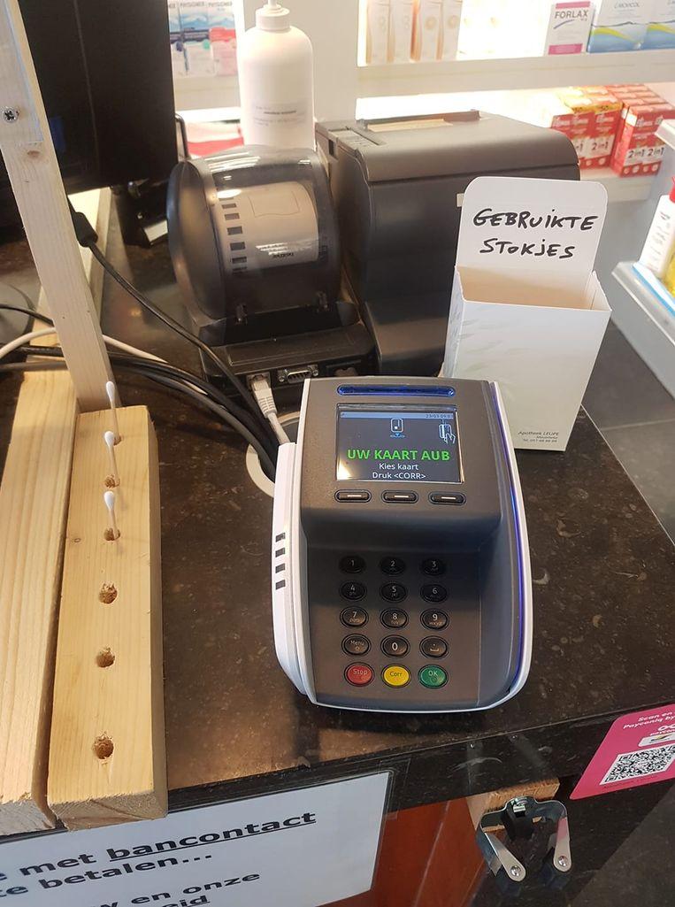 Oorstokjes om de pincode in het Bancontactapparaat in te geven bij apotheek Leupe.