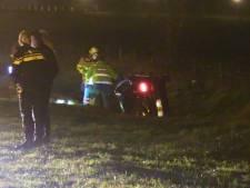Inzittenden auto zitten vast nadat voertuig op zijn kant in sloot belandt