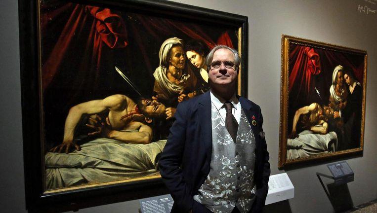 James Bradburne voor de vermeende Caravaggio uit Toulouse (links) en de kopie van Louis Finson (rechts). Beeld EPA
