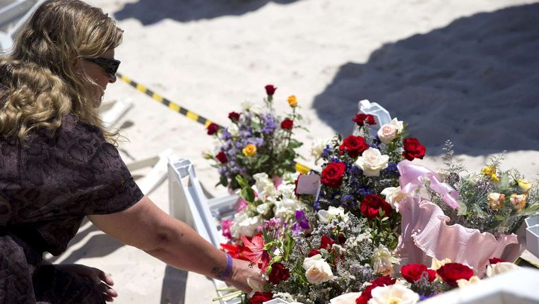 Een vrouw legt bloemen op het strand waar gisteren de aanslag plaatsvond.