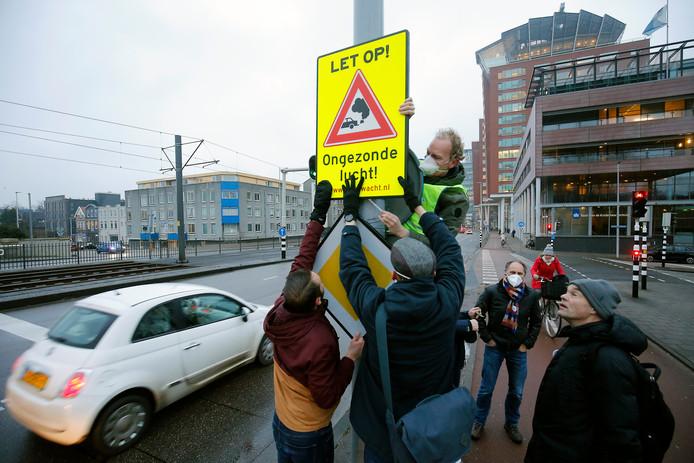 Utrechtse burgers plaatsen een waarschuwingsbord voor vervuilende lucht aan de Graadt van Roggenweg.