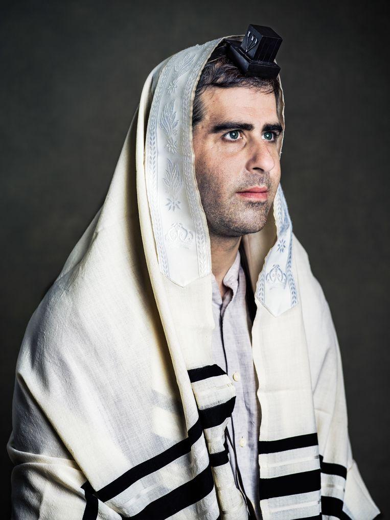 Nadav Schwartz draagt een tallit, een joods gebedskleed. Op zijn hoofd een tefilin, een gebedsriem. Die bestaat uit twee zwartleren doosjes waar lange leren banden aan zijn bevestigd. In de doosjes zitten rolletjes met Hebreeuwse teksten. Beeld Hadas Itzkovitch en Anya van Lit