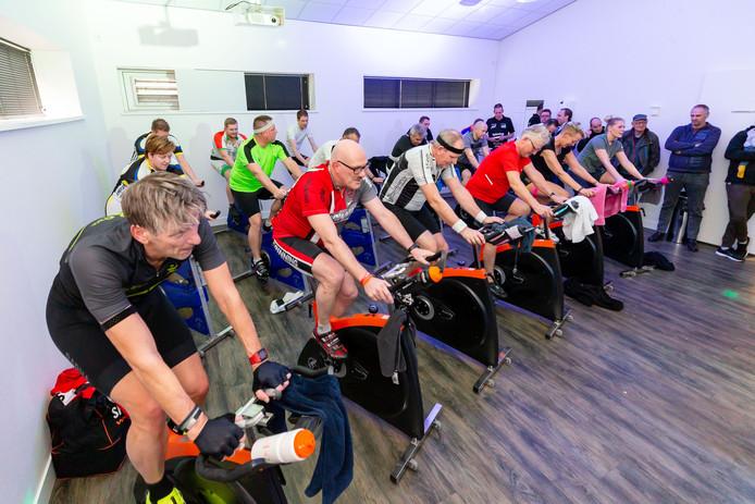 De deelnemers aan de spinningmarathon werken zich in het zweet. Zweten in de kleine zaal.