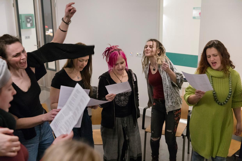Workshop zingen van traditionele Poolse liederen in combinatie met dans, door docent Karolina Rosocka (met arm omhoog) in Den Haag.