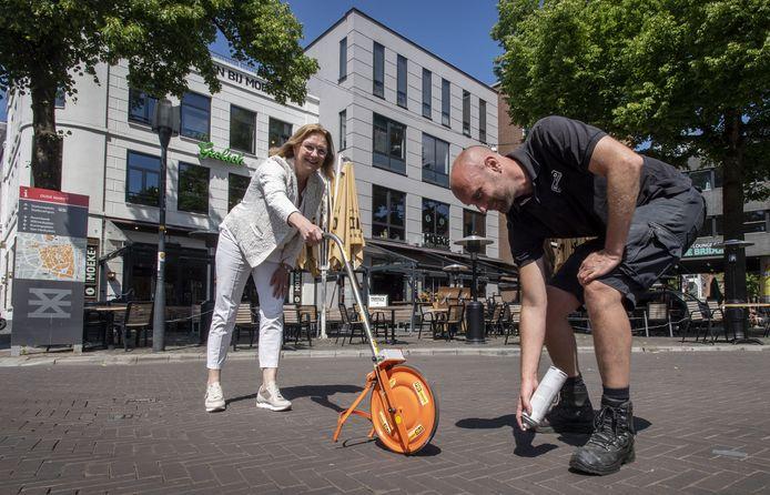 Wethouder June Nods en evenementenmanager Robin Hollander brengen de laatste belijning aan op de Oude Markt.