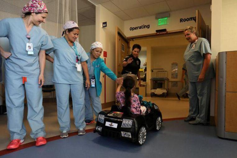 Andrea Destraio (5) geeft de medische staf van het ziekenhuis een high-five alvorens ze de operatiekamer binnenrijdt.