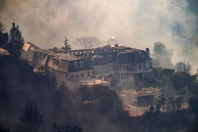 Een enorme villa in de wijk Bel Air wordt omringd door rook van de bosbranden die de stad Los Angeles teisteren.