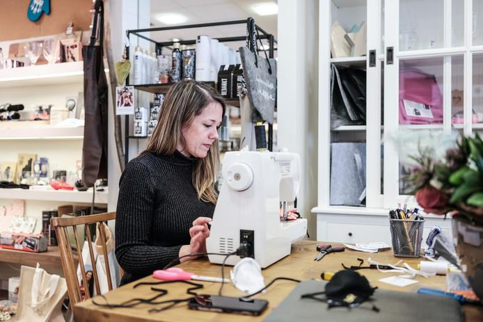 Susanne Janssen in haar cadeauwinkel  aan de Didamsestraat achter de naaimachine om mondkapjes te maken. Foto : Jan Ruland van den Brink
