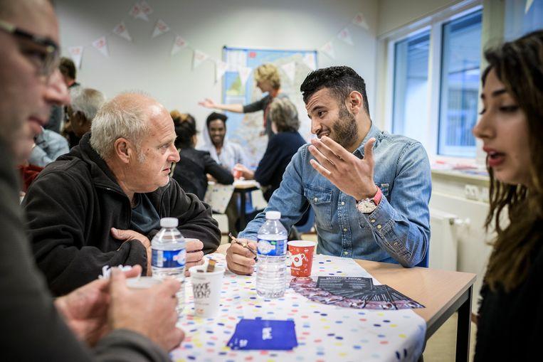 Open dag in het asielzoekerscentrum in Assen. Vluchtelingen drinken samen met bezoekers een kopje koffie in de ruimte van Vluchtelingenwerk. Beeld Kees van de Veen