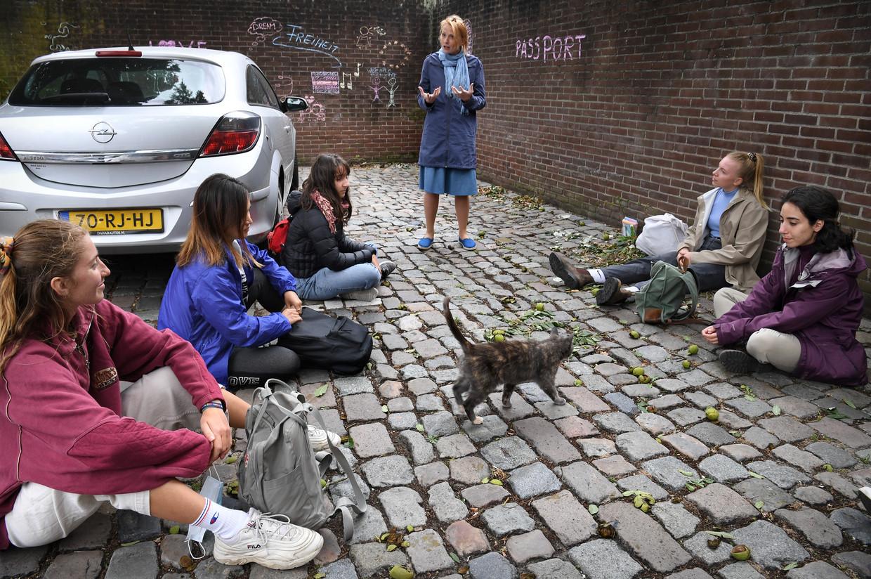 Studenten van het University College in Middelburg volgen een geschiedeniscollege over de Berlijnse Muur achter op een parkeerplaats in de stad. Beeld Marcel van den Bergh / de Volkskrant