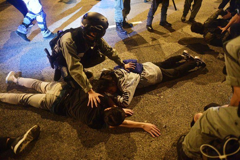 Politieagenten met studenten die zijn aangehouden na een ontsnappingspoging uit de Polytechnische Universiteit.  Beeld AFP