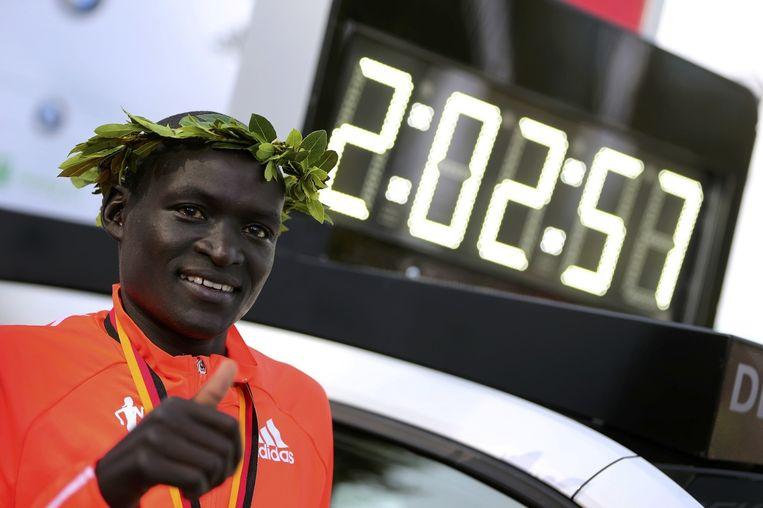Dennis Kimetto poseert naast de tijd die hij liep op de marathon van Berlijn waarmee hij een wereldrecord vestigde. Beeld reuters