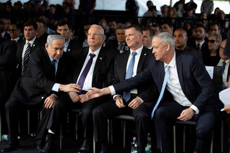 Benjamin Netanyahu (links) en  Benny Gantz reiken elkaar de hand tijdens een herdenkingsdienst voor oud-premier Rabin, op 10 november 2019. Beeld REUTERS