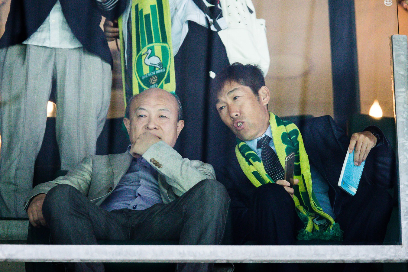 Hui Wang (L) op de tribune bij ADO Den Haag.