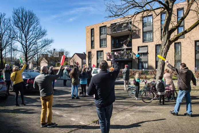 Familie en buurtgenoten van de jarige mevrouw Mali-Gijsberts zingen haar toe vanaf de parkeerplaats van verpleeghuis De Vlechting in de Nijmeegse wijk Zwanenveld.