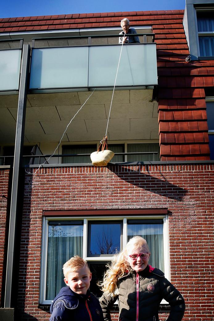Iris en Fedde brengen tekeningen en lekkers bij hun overgrootopa Frits Maaijen (86). Vanuit zijn woning in Hof van Ammers in Groot-Ammers hengelt hij het mandje naar boven.
