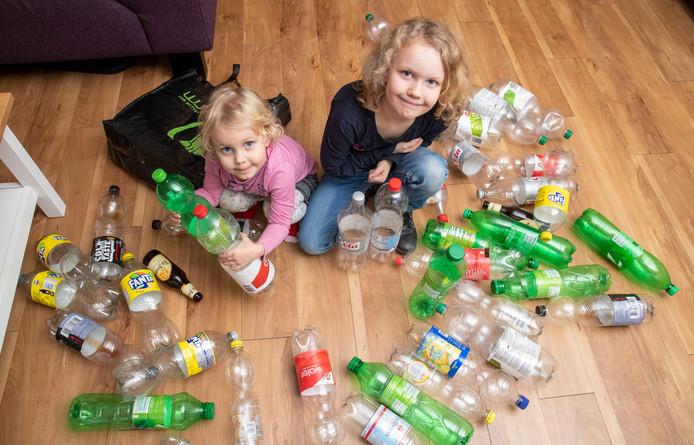 Zusjes Elvera en Alyssa met een deel van hun ingezamelde flessen.