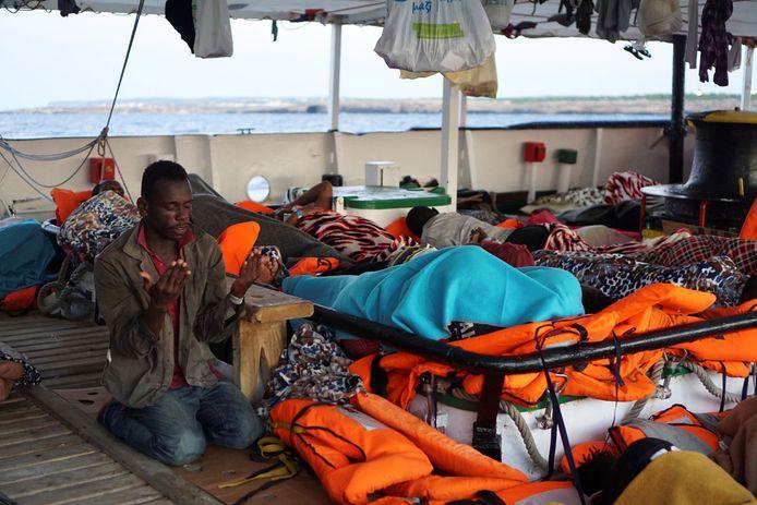 Een migrant bidt aan boord van de Open Arms.