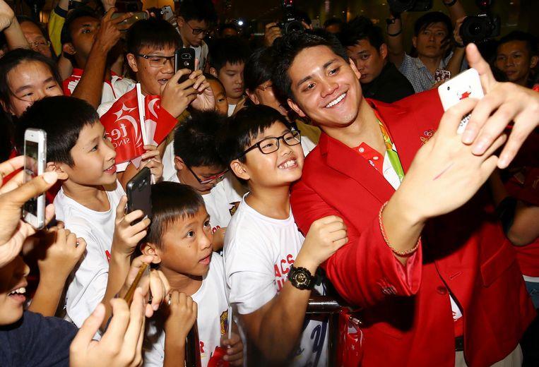 De eerste gouden medaillewinnaar van Singapore Joseph Schooling maakt een selfie met een jonge fan. Beeld null