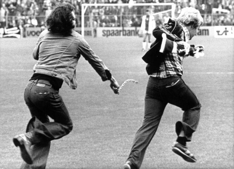 Ongeregeldheden tijdens de wedstrijd Ajax-Utrecht (7-0) in 1976. Een Utrecht-supporter gaat een Ajax-fan te lijf met een ketting. Beeld ANP