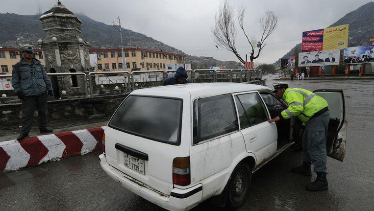 De politie controleert een auto bij een wegblokkade als veiligheidsmaatregel voor de verkiezingen. Beeld getty