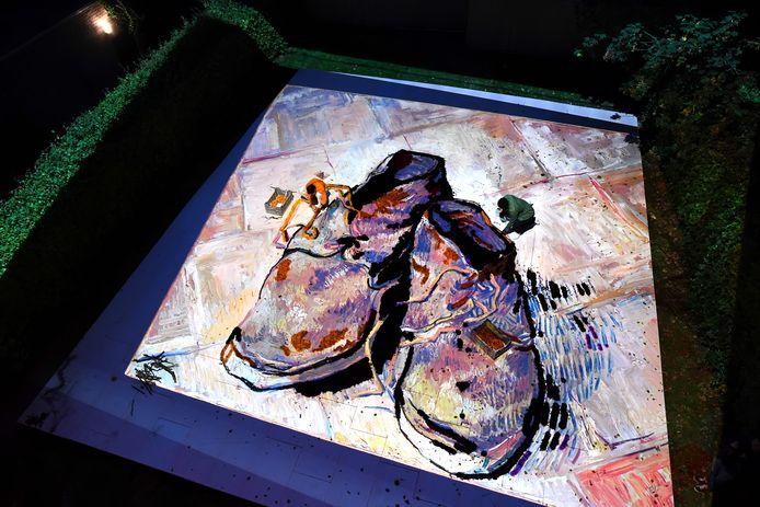 Medewerkers van Vik Muniz aan de slag met de dahlia-reproductie die in de ruin van het Van GoghHuis wordt gemaakt. Op de projectie die op de grond verschijnt worden dahlia's in de veters geprikt