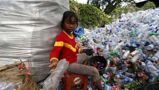 Een Indonesisch meisje recyclet plastic
