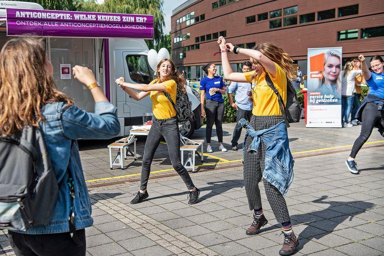 Studenten van de Hogeschool Leiden doen samen met hun mentoren een dansje bij de anticonceptiebus. Beeld Guus Dubbelman / de Volkskrant