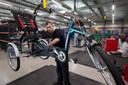 Een van de personeelsleden werkt aan een aangepaste fiets.