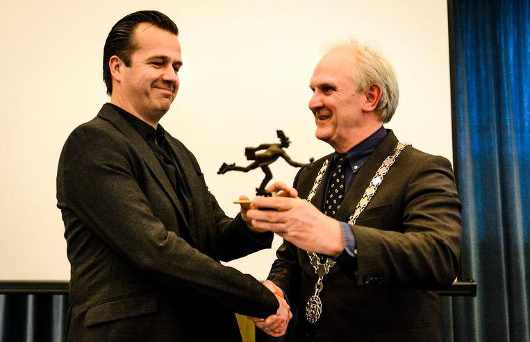 Burgemeester Pieter Broertjes (R) van Hilversum overhandigd Bas Haan zijn prijs tijdens de uitreiking Journalist van het Jaar. Beeld anp